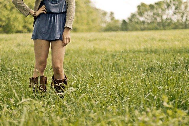Žena s holými nohami stojaca vo vysokej tráve