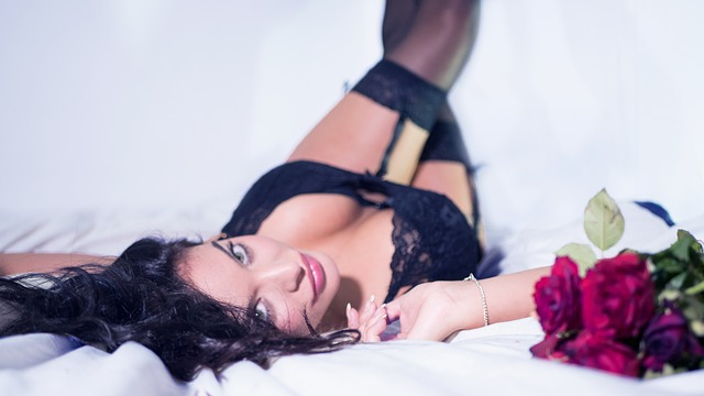 Žena v čiernej erotickej bielizni leží na posteli s nohami opretými o stenu