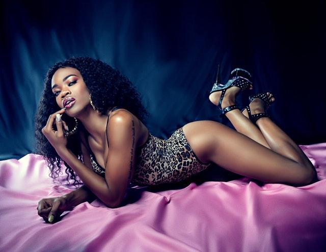 Žena s kučeravými vlasmi, v spodnej bielizni s leopardím vzorom, leží na ružovej posteli