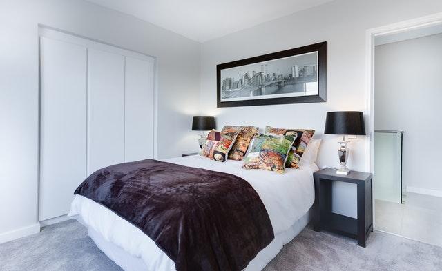 Spálňa s manželskou posteľou, na ktorej je vysoký matrac prikrytý bielou dekou