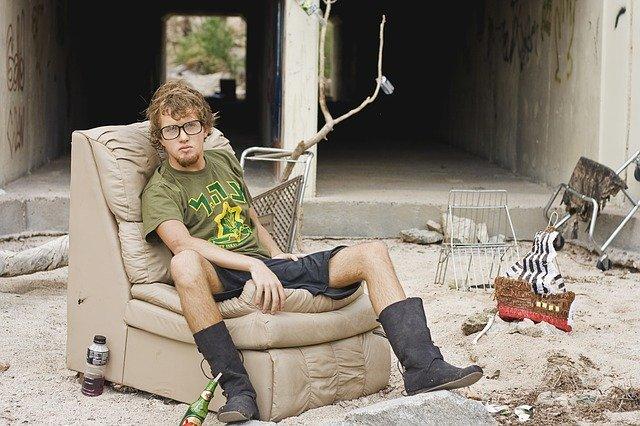 Chlapec v zelenom tričku sedí na kresle na smetisku.jpg